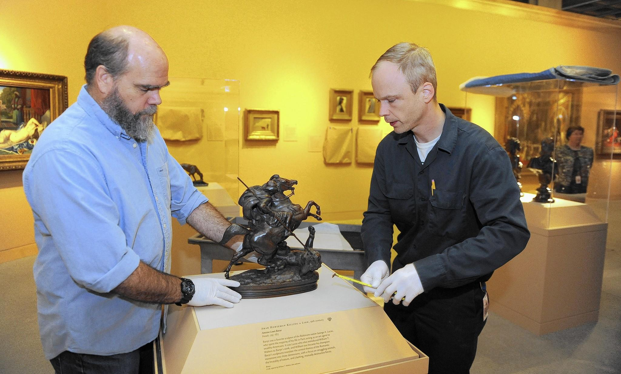 "Mike McKee, left, a senior art handler, and collections technician Craig Bowen check the placement of the bronze sculpture ""Arab Horseman Killing A Lion"" by Antoine-Louis Barye that is part of the new exhibit ""From Rye to Raphael: The Walters Story"" at the Walters Art Museum."