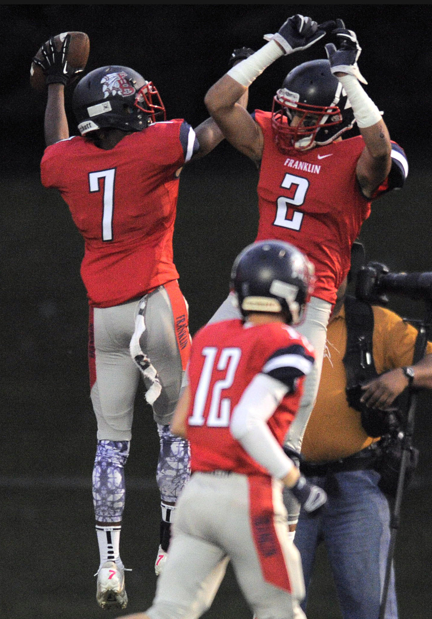 Franklin's Steven Smothers (7) leaps with Mohammad Hussain (2) above Brian Doyle (12) following a touchdown.