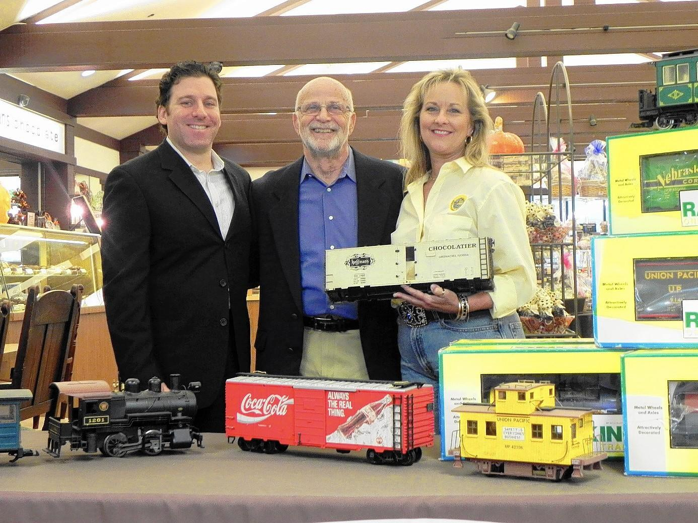 From left, Jarrett Levan, president of BBX Capital; Paul Hoffman, founder of Hoffman's Chocolate; and Paige Poole, manger of Yesteryear Village, are excited about Yesteryear Village's newest exhibit, a Railroad History Museum.