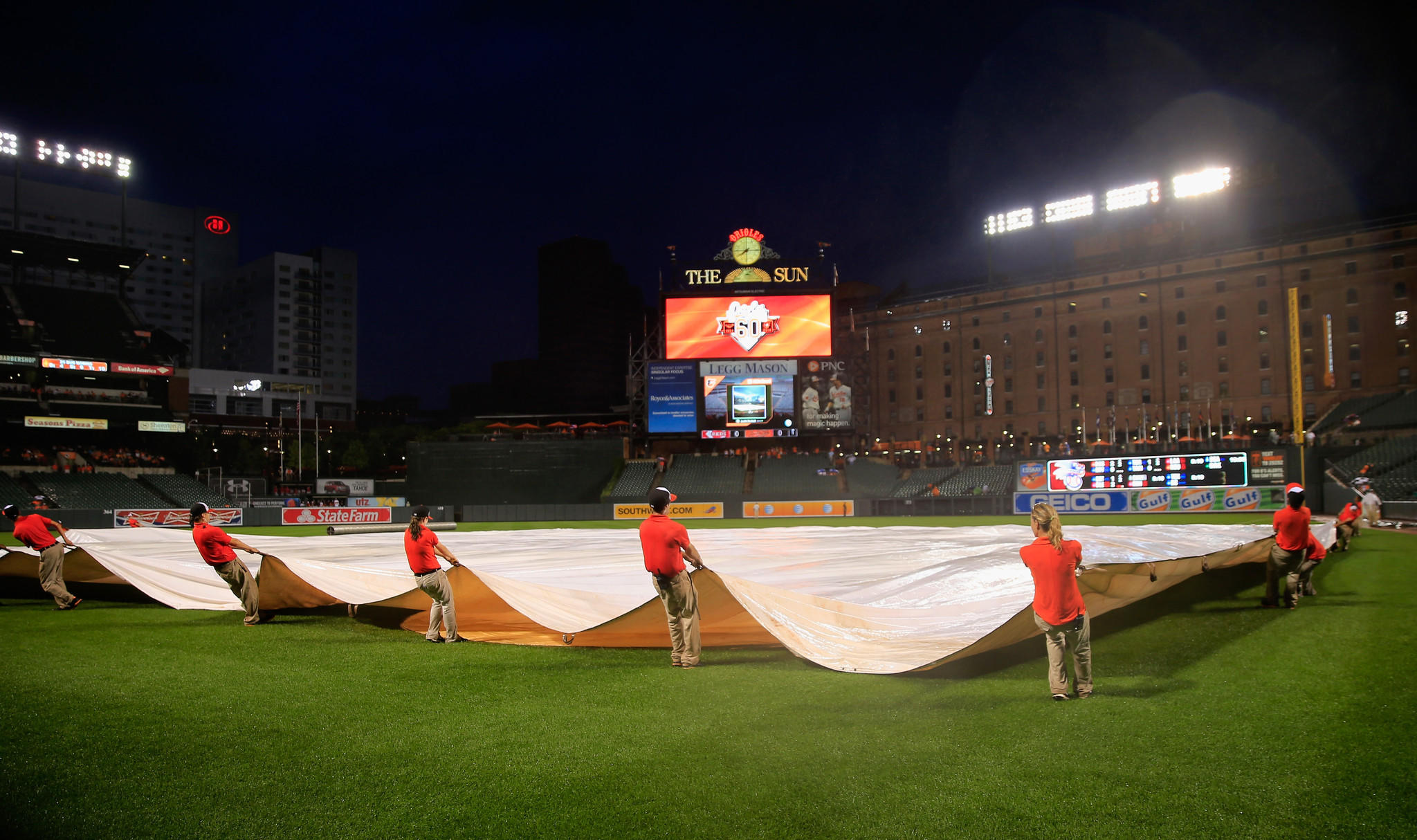 Members of the grounds crew pull the tarp on the field during a rain delay in the first inning of the Cincinnati Reds and Baltimore Orioles game at Oriole Park at Camden Yards on September 2.