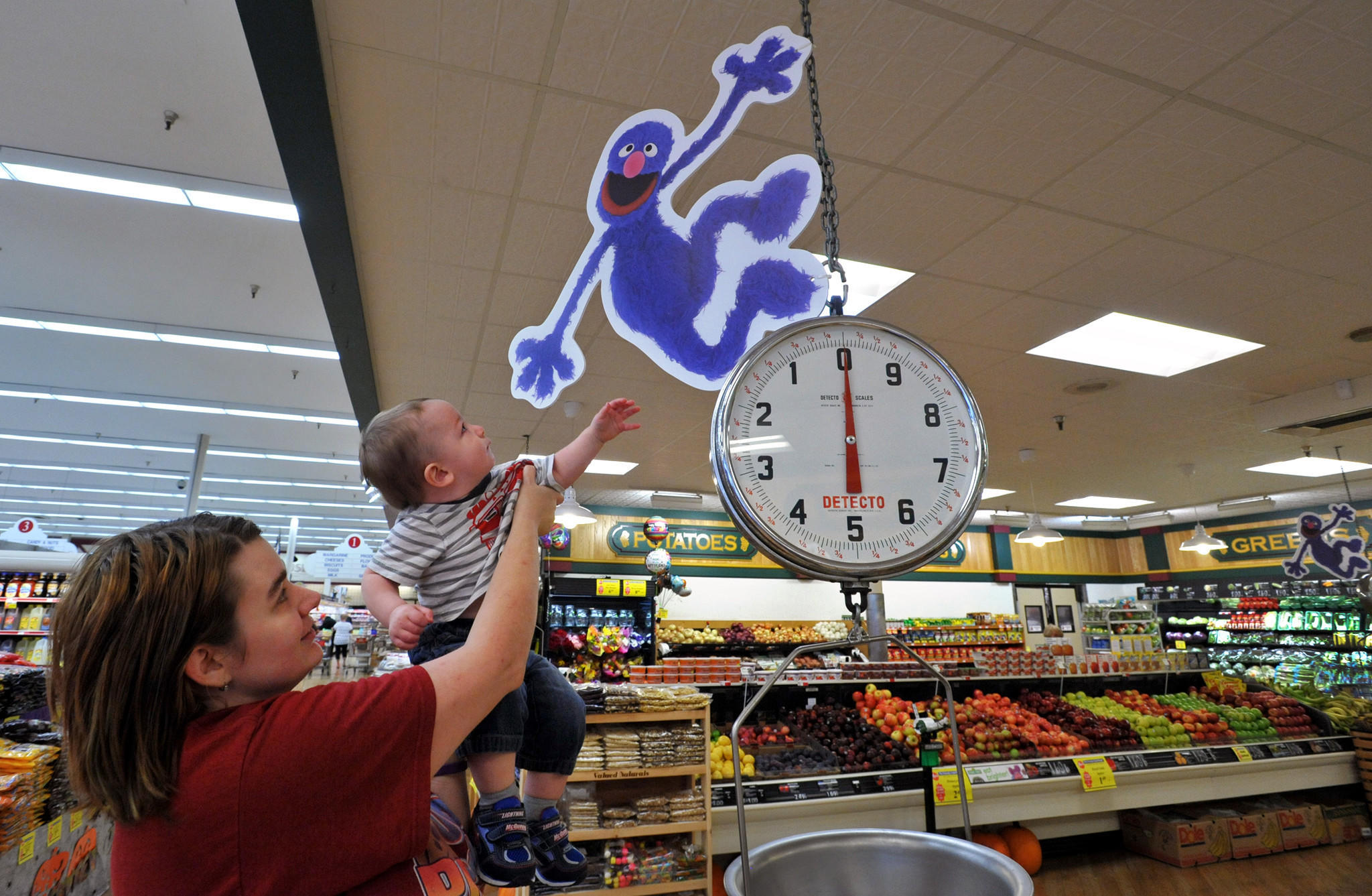 "Dundalk, MD - 9/29/14 - Laura Shelton of Dundalk hoists her one-year old son, Kevin Shelton, Jr. closer to a Grover sign as they shopped at the Mars store on Wise Avenue. Mars is the first supermarket in Maryland to participate in the ""Eat Brighter"" campaign from the produce marketing association, which teamed up with the Sesame Street Workshop to encourage healthier eating among pre-schoolers. Amy Davis /Baltimore Sun - #6880"