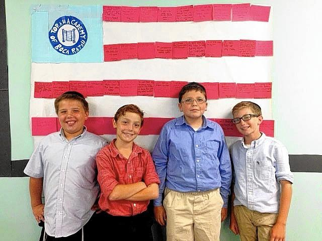 Torah Academy of Boca Raton middle-school students (from left) Ben Abrams, Yehuda Greenwald, Moshe Glazer and Azi Galbut in front of a flag made up of student pledges of kindness to honor 9-11 victims.