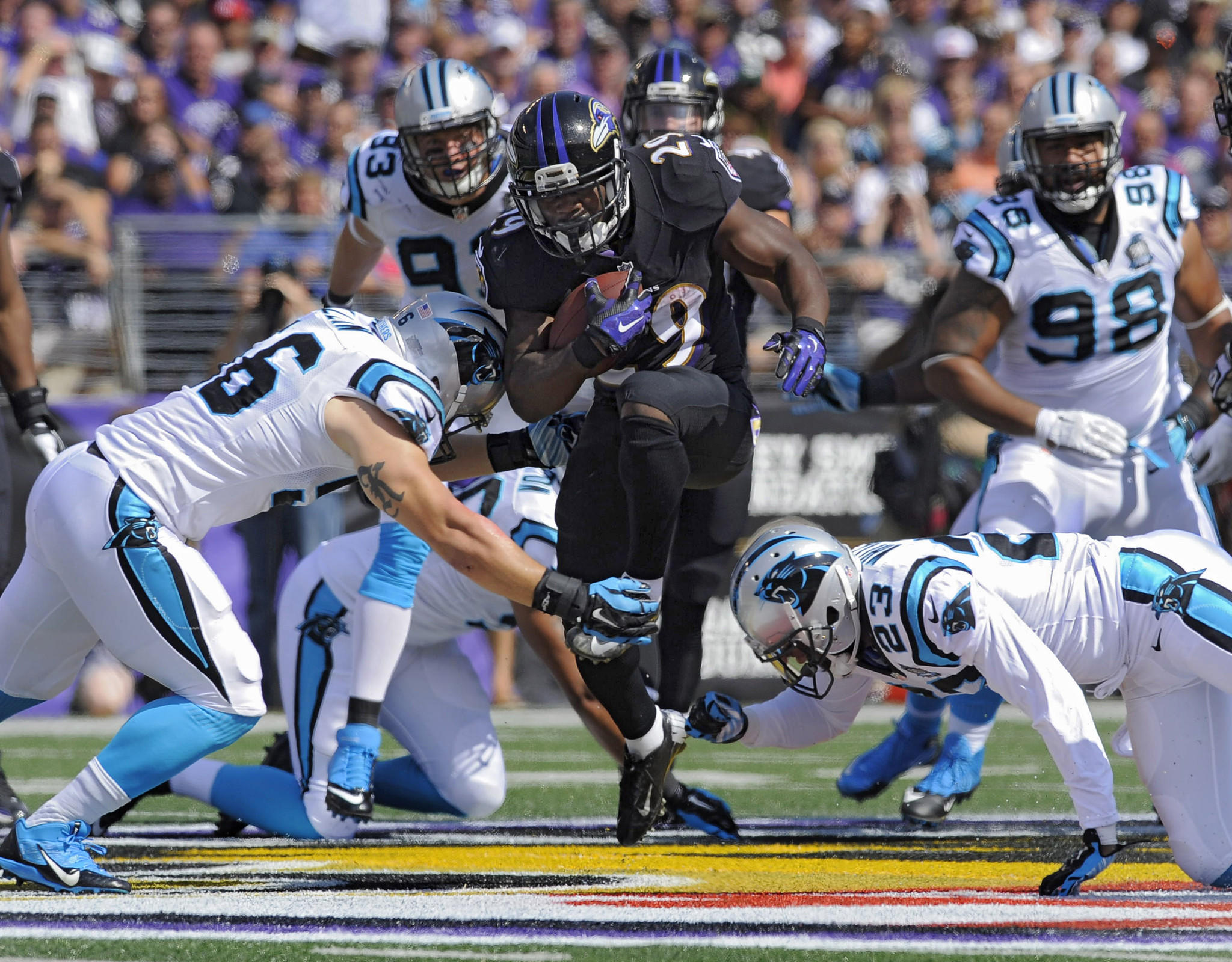 Panthers linebacker A.J. Klein (left) and cornerback Melvin White (23) converge on Ravens running back Justin Forsett, who gains first down yardage during the first quarter.