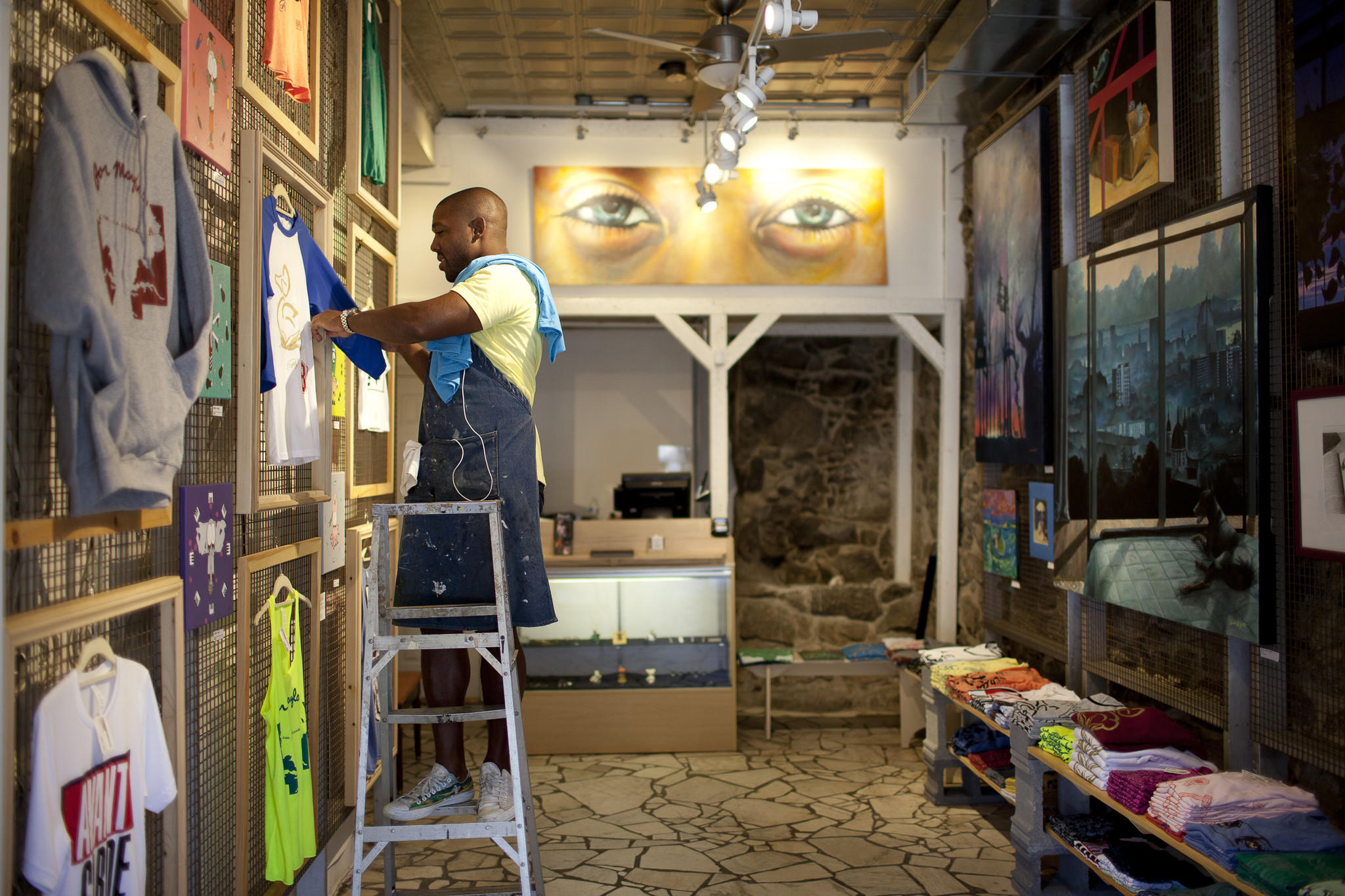 Jereme Scott changes out a t-shirt at his store, Cotton Duck Art & Apparel, in Ellicott City.