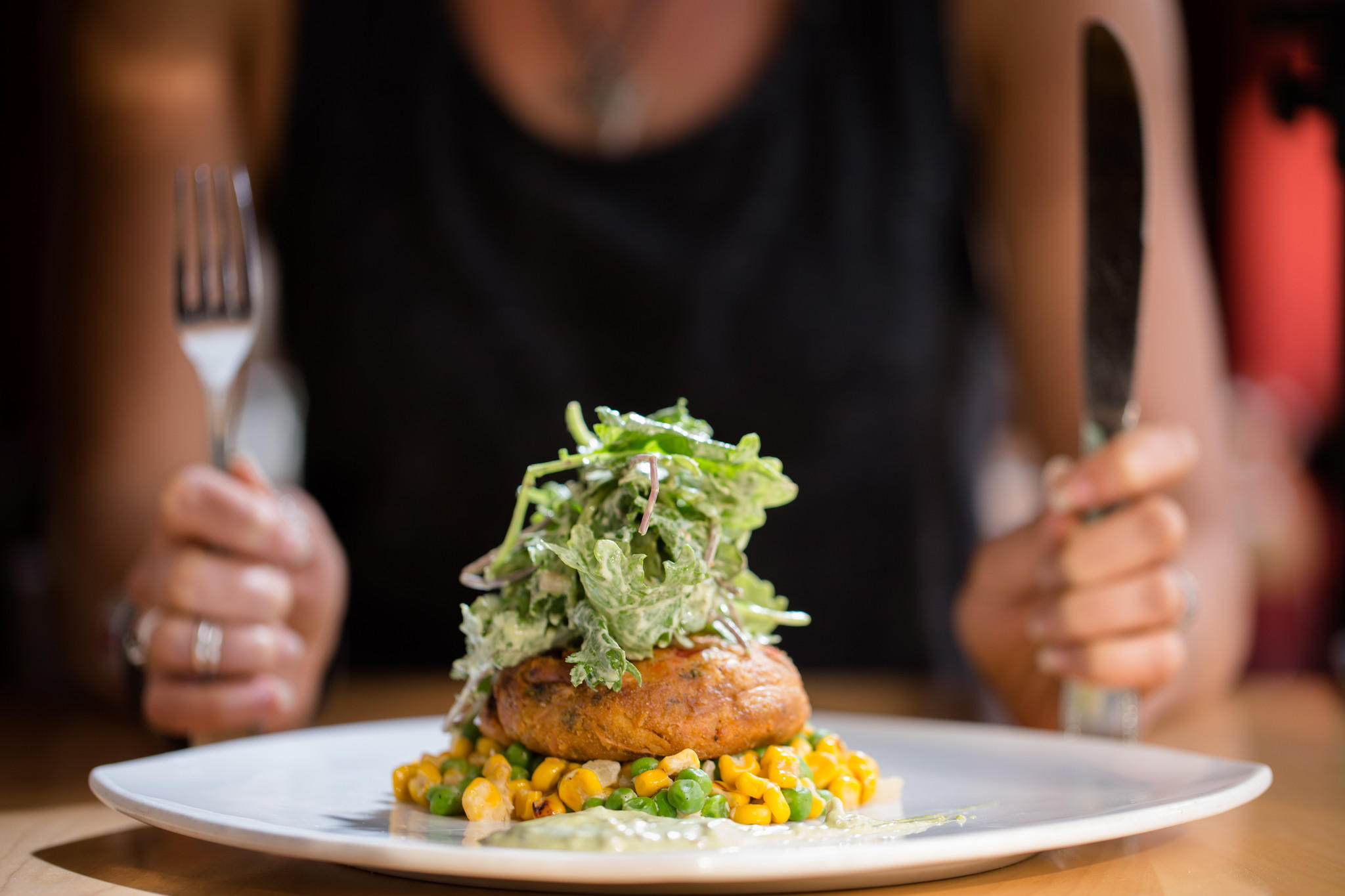"""Hearts of palm """"crab cake"""" made from roasted red pepper and caramelized onion, hearts of palm, with roasted corn and green pea succotash and baby kale salad tossed in basil caper remoulade."""