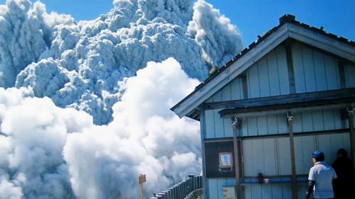 In this photo taken Sept. 27, 2014 by 59-year-old hiker Izumi Noguchi one of at least 47 who fell victim to the eruption of Mount Ontake, a hiker watches dense plumes of gases and ash gushing out from the summit crater as the volcanic mountain starts to erupt.