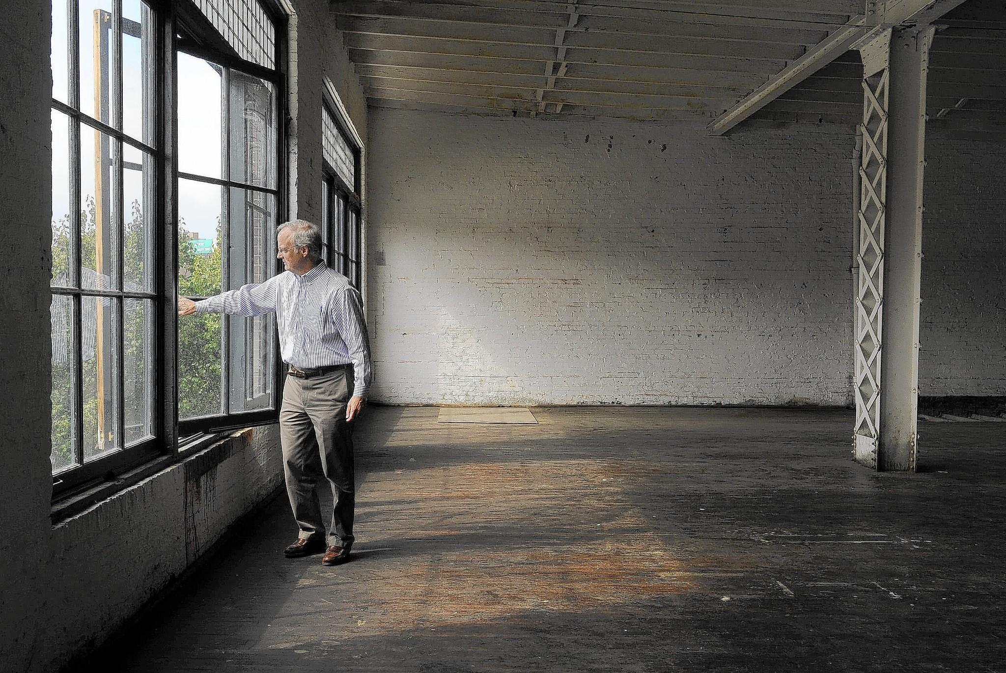 Mac MacLure of the Baltimore Arts Realty Corporation opens a third floor window in the former 1920s auto showroom and garage that his company is converting to artists' studios and businesses.