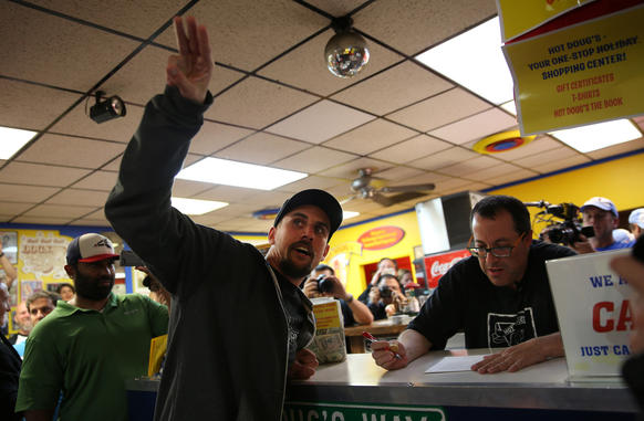 Joe Hehl, left, the last customer who had been waiting since 6:45 am at Hot Doug's, takes his order from owner Doug Sohn, on the final day of business for the restaurant.