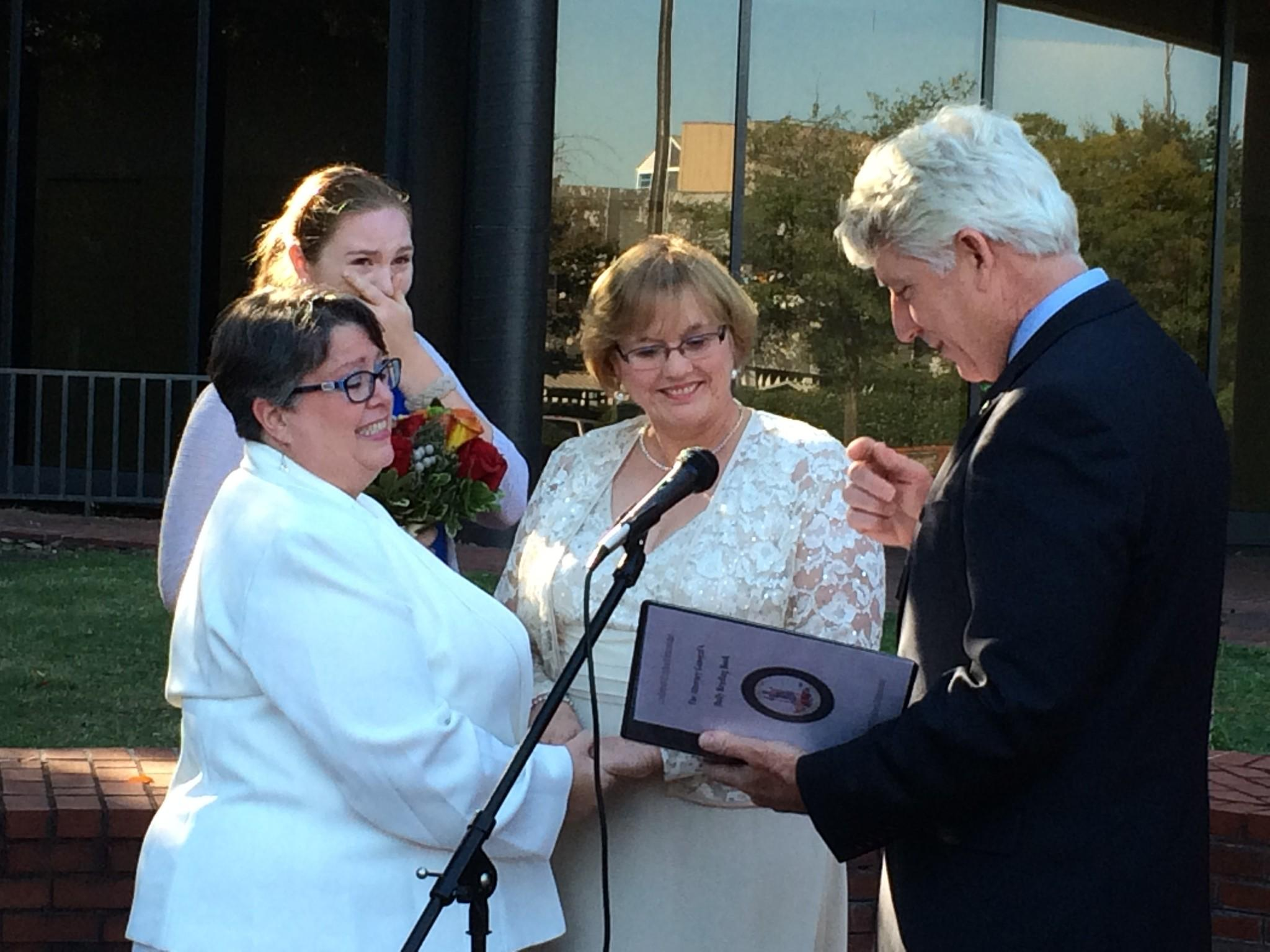 Carol Schall and Mary Townley renew their wedding vows Monday afternoon outside the circuit courthouse in Richmond. Attorney General Mark Herring officiated. Emily, their daughter, shed a few tears. The couple was originally married in California, but with Monday's Supreme Court action, their marriage is now legal in Virginia.