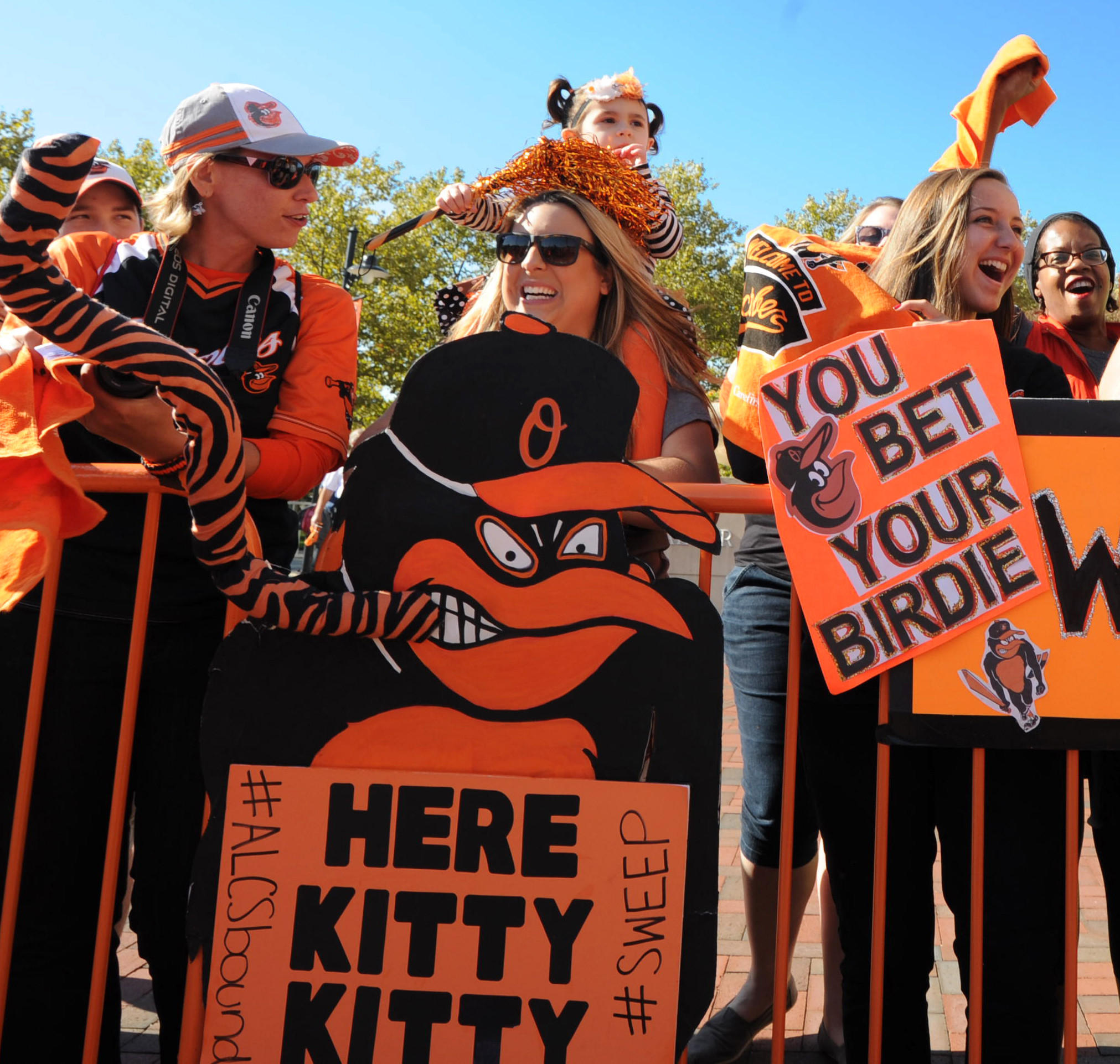 "Chrissy Forbes, center, from Abingdon brought her daughter Gabriella, 2 1/2 and the ""Kitty"" sign in front of her to Oriole Park for the Orioles' arrival after their weekend sweep of the Detroit Tigers."