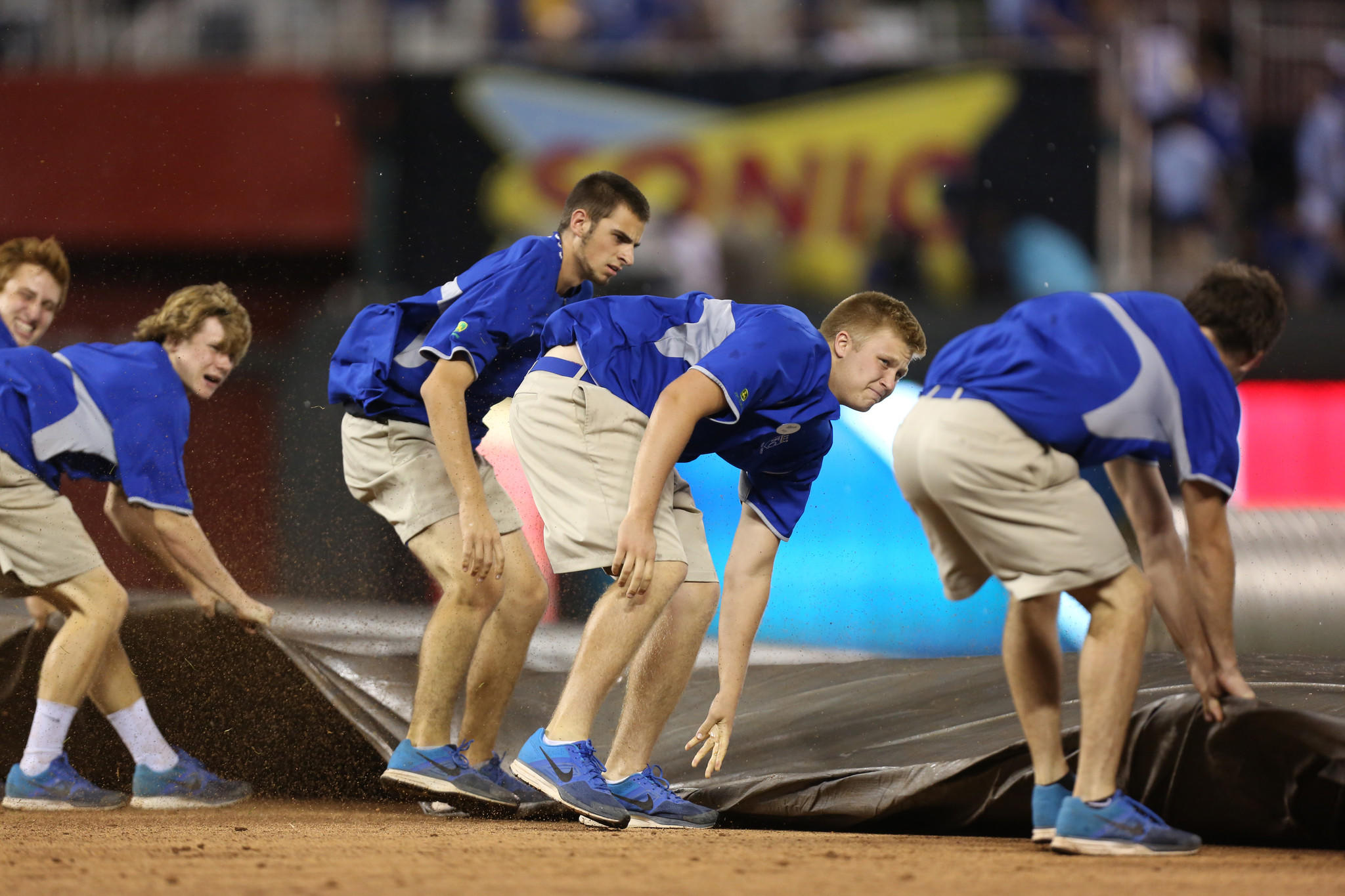 Kansas City Royals' grounds crew bring out the infield tarp as they prepare for a rain storm in the tenth inning during a game between Cleveland Indians and Kansas City Royals at Kauffman Stadium on August 31.