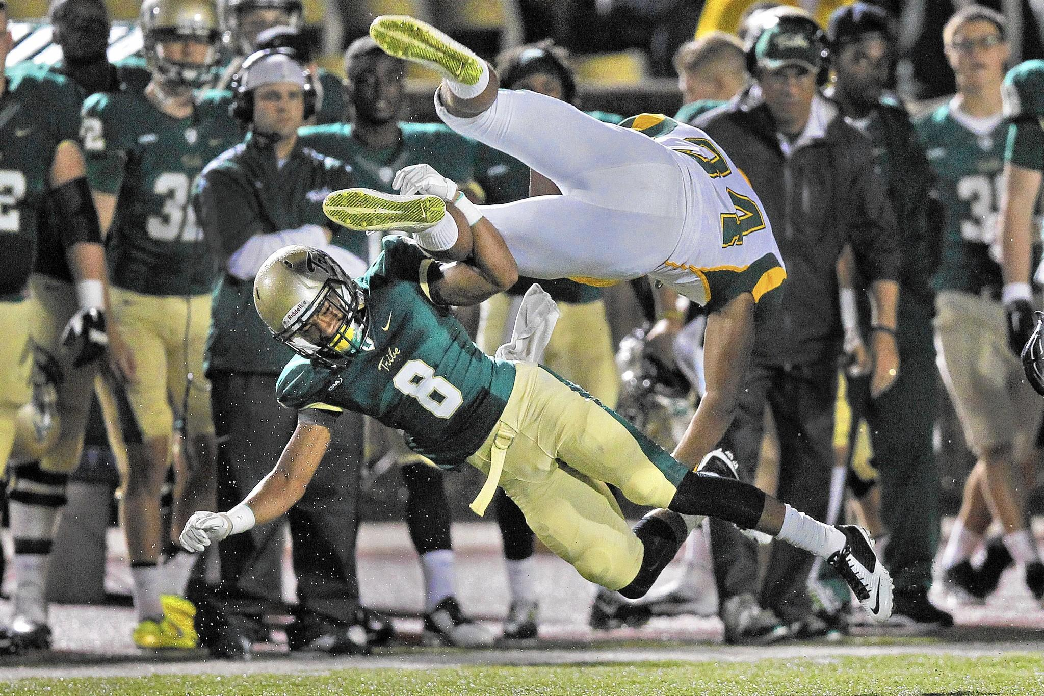 William and Mary's Trey Reed, bottom, tackles and sends Norfolk State's Aaron Daniels into the air during Saturday's game at Zable Stadium.