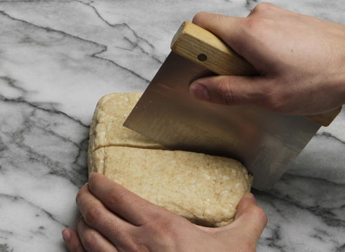 Take the slab of chilled dough from the refrigerator and divide it in half.