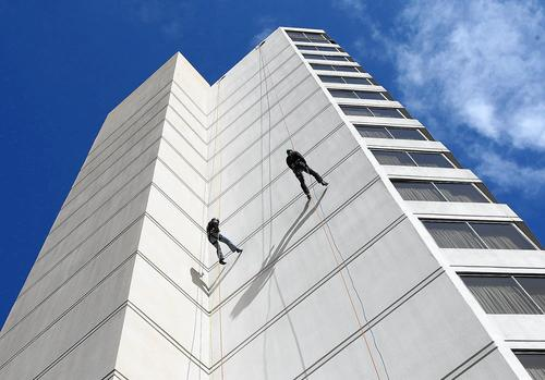 Two participants in the Over the Edge experience come down the side of the Irvine Marriott hotel on Friday. Rappellers were asked to raise $1,000 each to benefit the Orange County Council of the Boy Scouts of America.