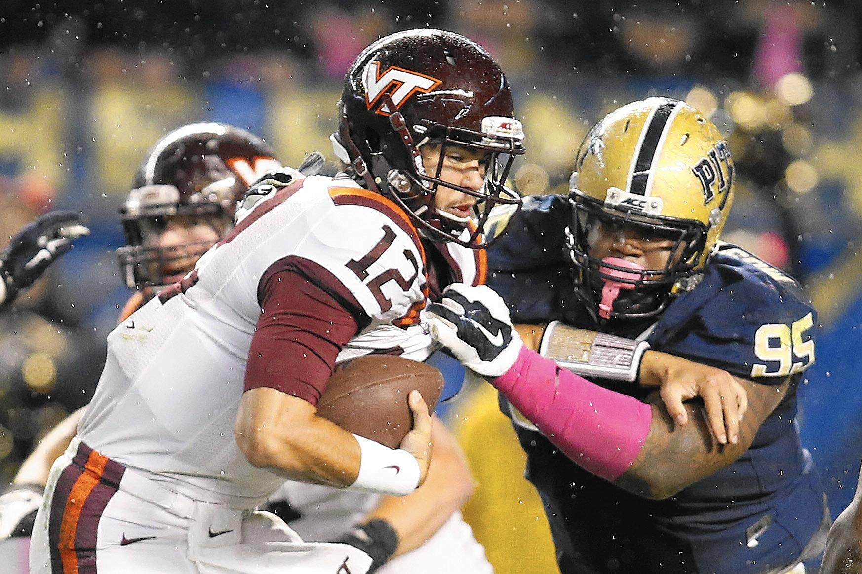 Virginia Tech quarterback Michael Brewer is tackled by Pittsburgh defensive lineman Khaynin Mosley-Smith on Thursday in Pittsburgh.
