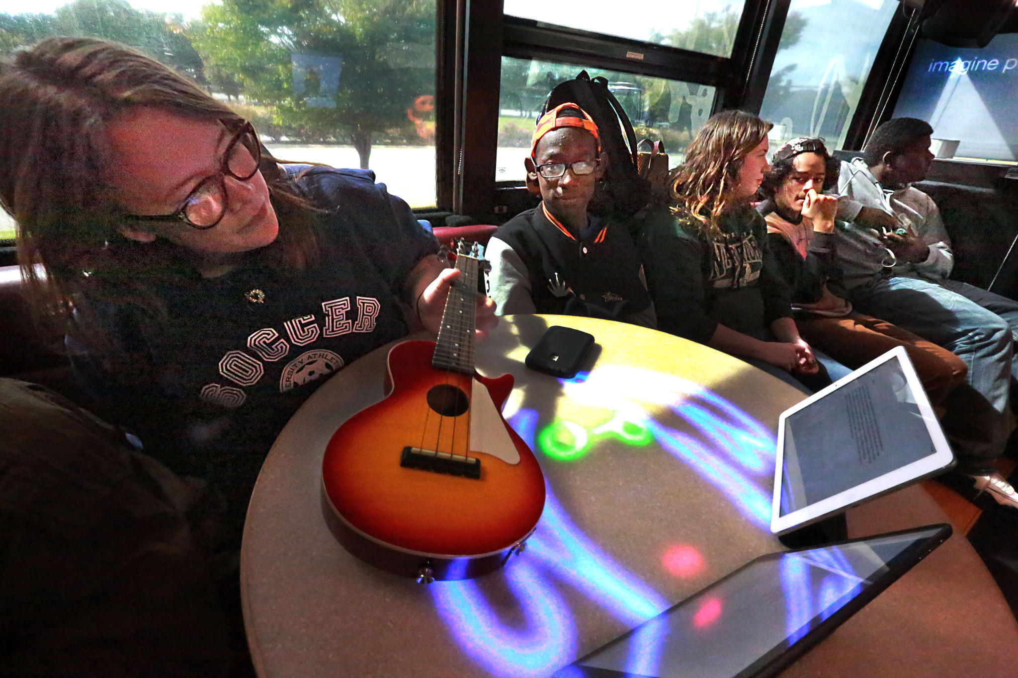 Students from Hampton City Schools sit on the John Lennon Music Education Bus on Monday.
