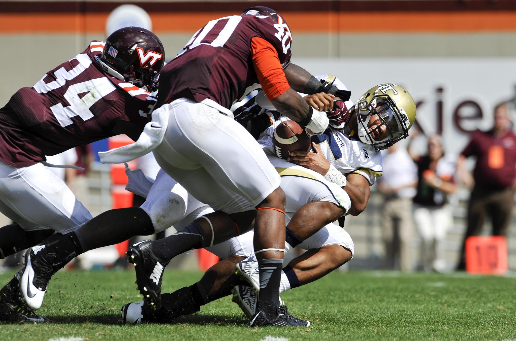 BLACKSBURG, VA - SEPTEMBER 20: Quarterback Justin Thomas #5 of the Georgia Tech Yellow Jackets fumbles after being hit by linebacker Deon Clarke #40 and rover Kyshoen Jarrett #34 of the Virginia Tech Hokies in the second half at Lane Stadium on September 20, 2014 in Blacksburg, Virginia. The play had previously been blown dead for forward progress. Georgia Tech defeated Virginia Tech 27-24. (Photo by Michael Shroyer/Getty Images) ORG XMIT: 511821687