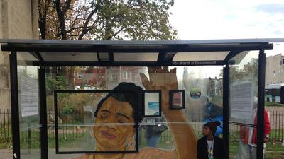 Local street artist Nether creates work on bus stop where video captured police beating citizen