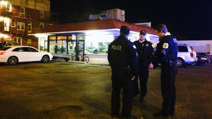 Police officers gather outside of Kevin's Hamburger Heaven where a shooting happened Friday morning. (Alexandra Chachkevitch, Chicago Tribune)