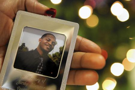 Michelle Watson holds an ornament with a photo of her brother Jacoby Plummer. Brian van der Brug / Los Angeles Times