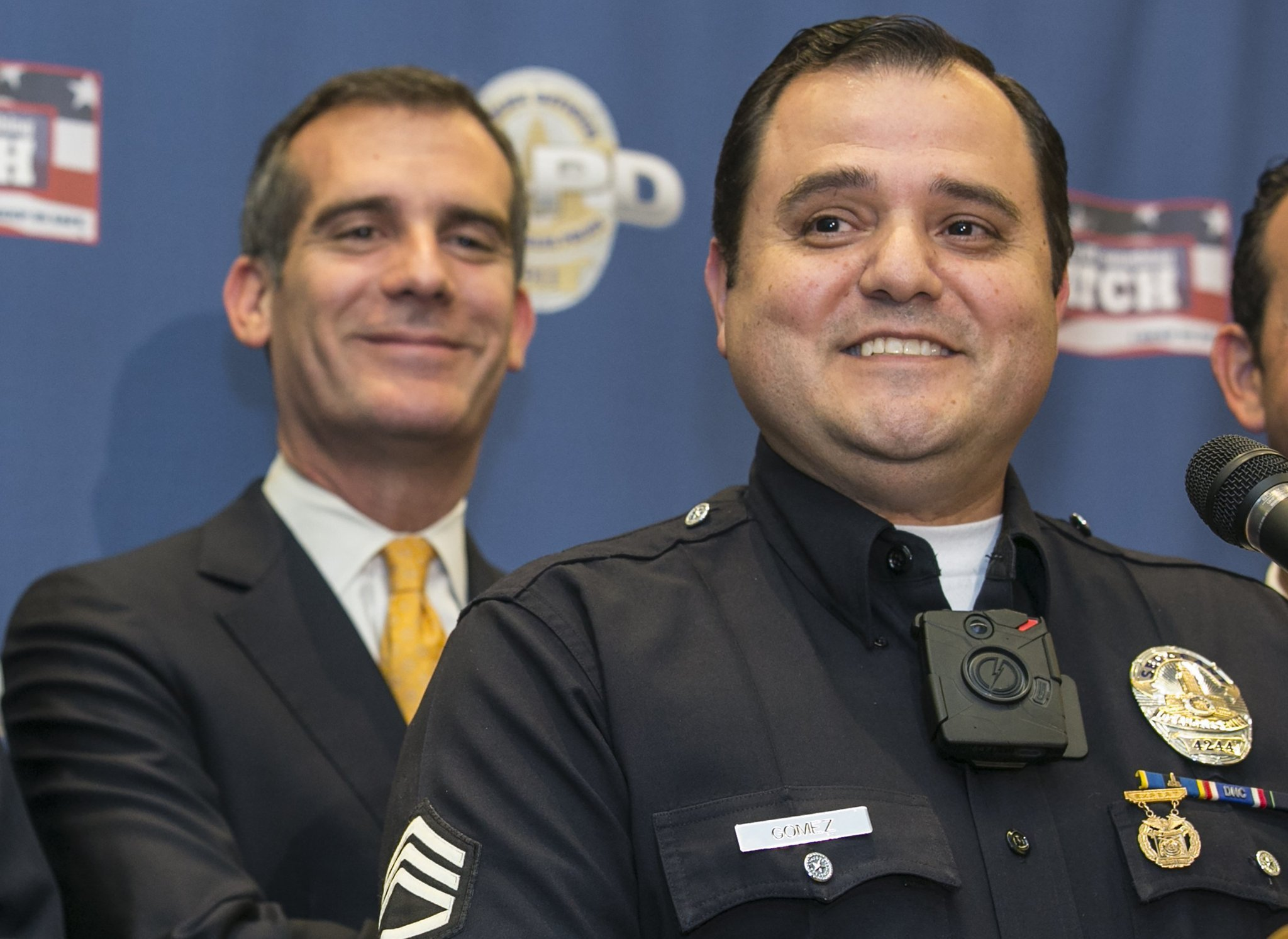 L.A. Police Sgt. Dan Gomez, right, wears an on-body video camera as he takes questions about the technology at a news conference. (Damian Dovarganes / Associated Press)