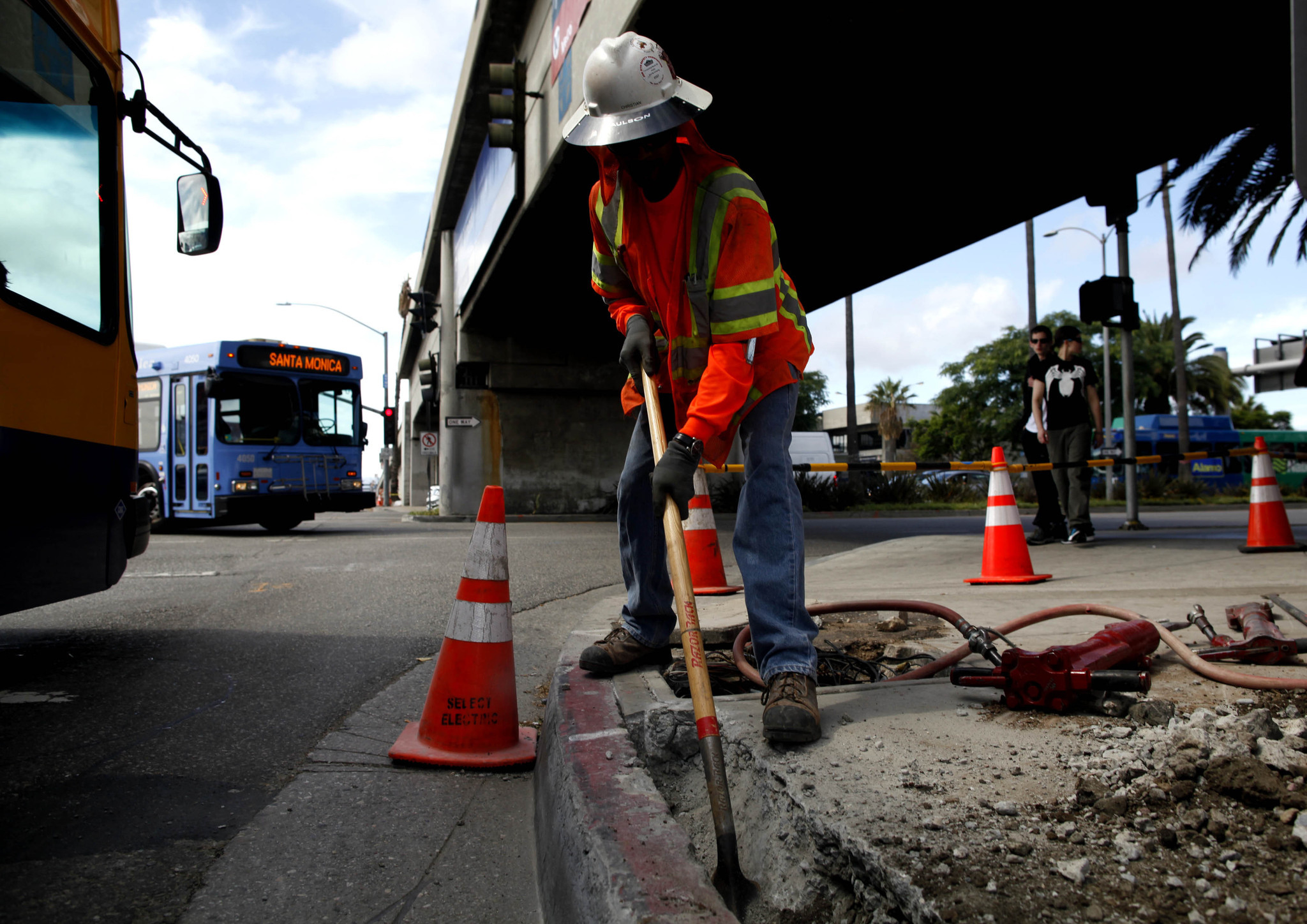 A construction worker digs next to a roadway at Los Angeles International Airport. (Barbara Davidson / Los Angeles Times)