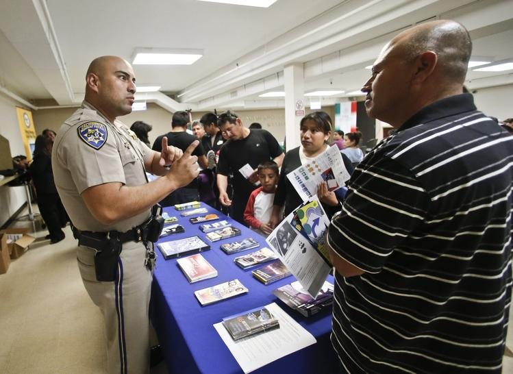 A California Highway Patrol officer explains how immigrants in the country illegally can obtain driver's licenses under a state law enacted in 2013. (Lenny Ignelzi / Associated Press)