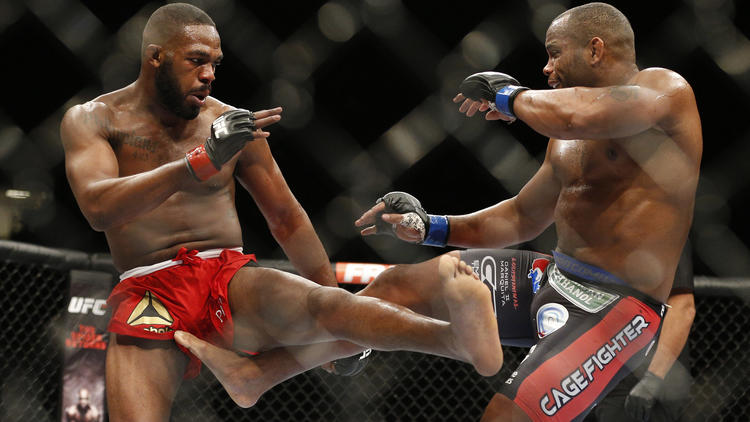 Jon Jones, left, and Daniel Cormier trade kicks in the middle of the octagon at UFC 182 on Jan. 3, 2015. (John Locher / Associated Press)