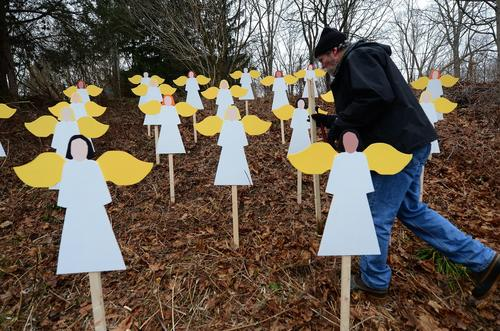 Art teacher Eric Mueller sets up 27 wooden angel cutouts in memory of the shooting victims Sunday morning.