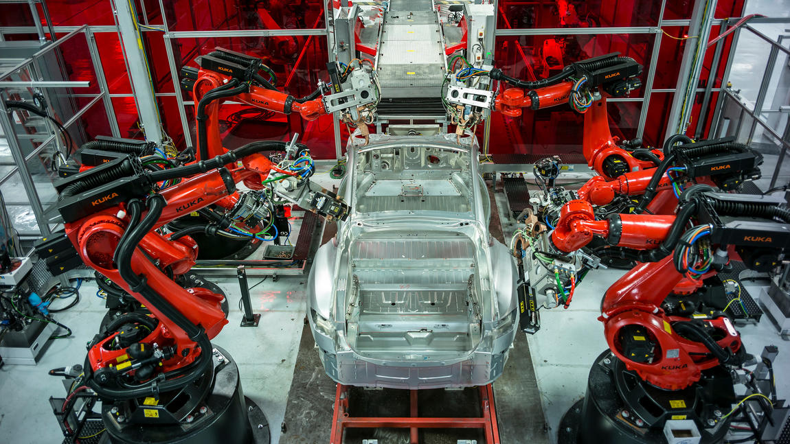 Robots at the Tesla factory putting together a car
