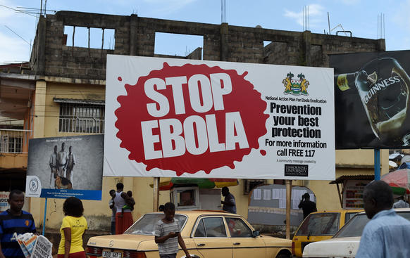 A picture taken Nov. 7 shows people walking past a billboard with a message about ebola in Freetown, Sierra Leone.