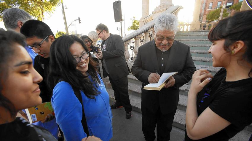 Author Luis Rodriguez signs books for the Mendez High School Reading Club, the kind of activity that the school hopes will attract new students. (Genaro Molina / Los Angeles Times)