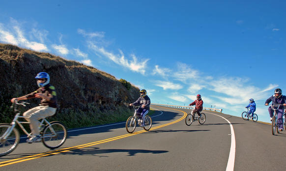 <p>Riders cross back over the road after a scenic viewing stop on their sunrise bike trek down Haleakala, a nearly 10,000-foot volcano on Maui. Every year, thousands of bicyclists take the 27-mile ride to the sea.</p>