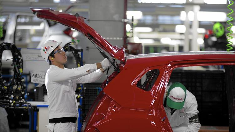 Employees assemble cars in Mexico. [Eduardo Verdugo, Associated Press)