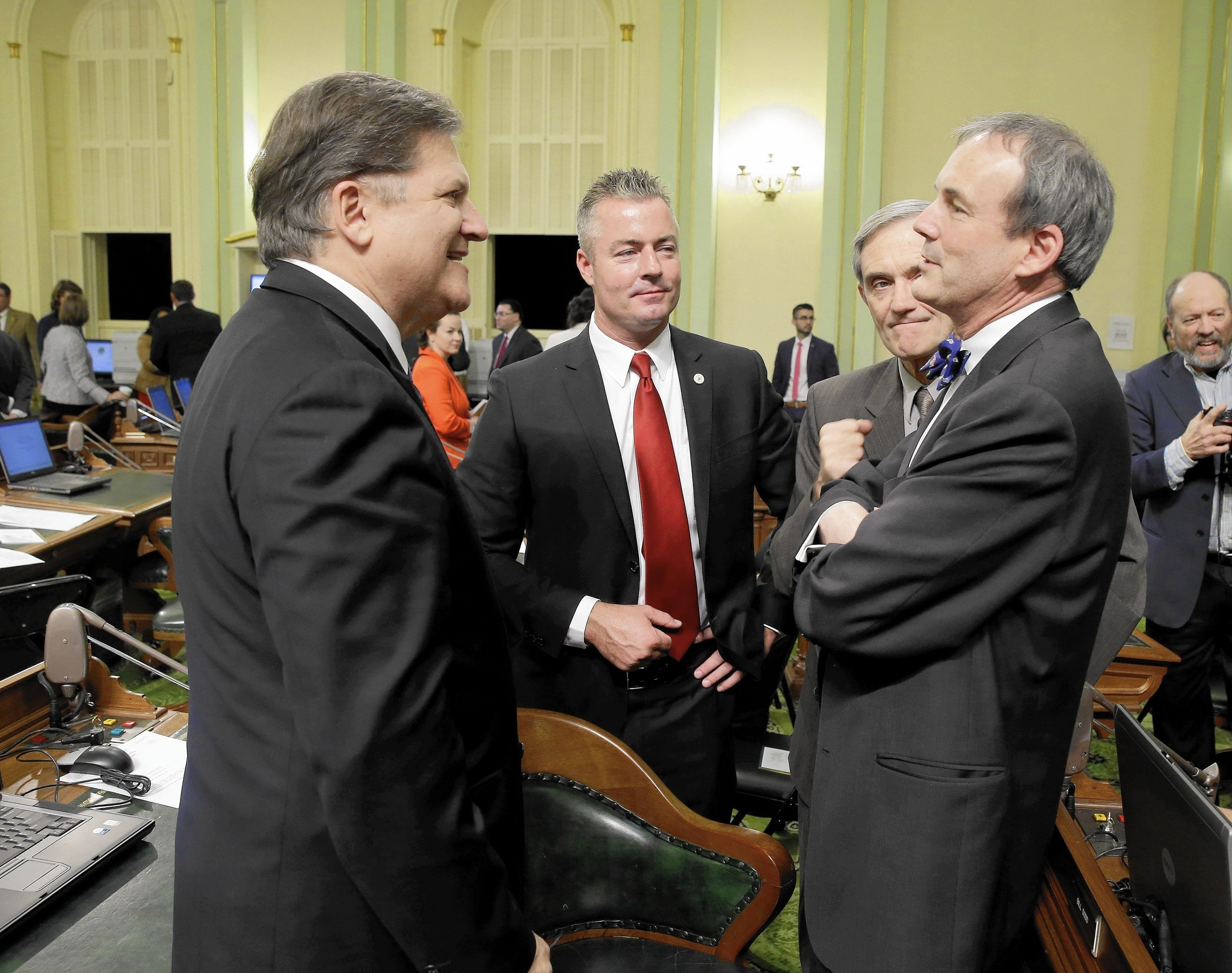 Assemblyman Travis Allen, center in red tie, is flanked by State Sen. Bob Hertzberg (D-Van Nuys) and Charles Munger Jr. in 2014. (Rich Pedroncelli / Associated Press)