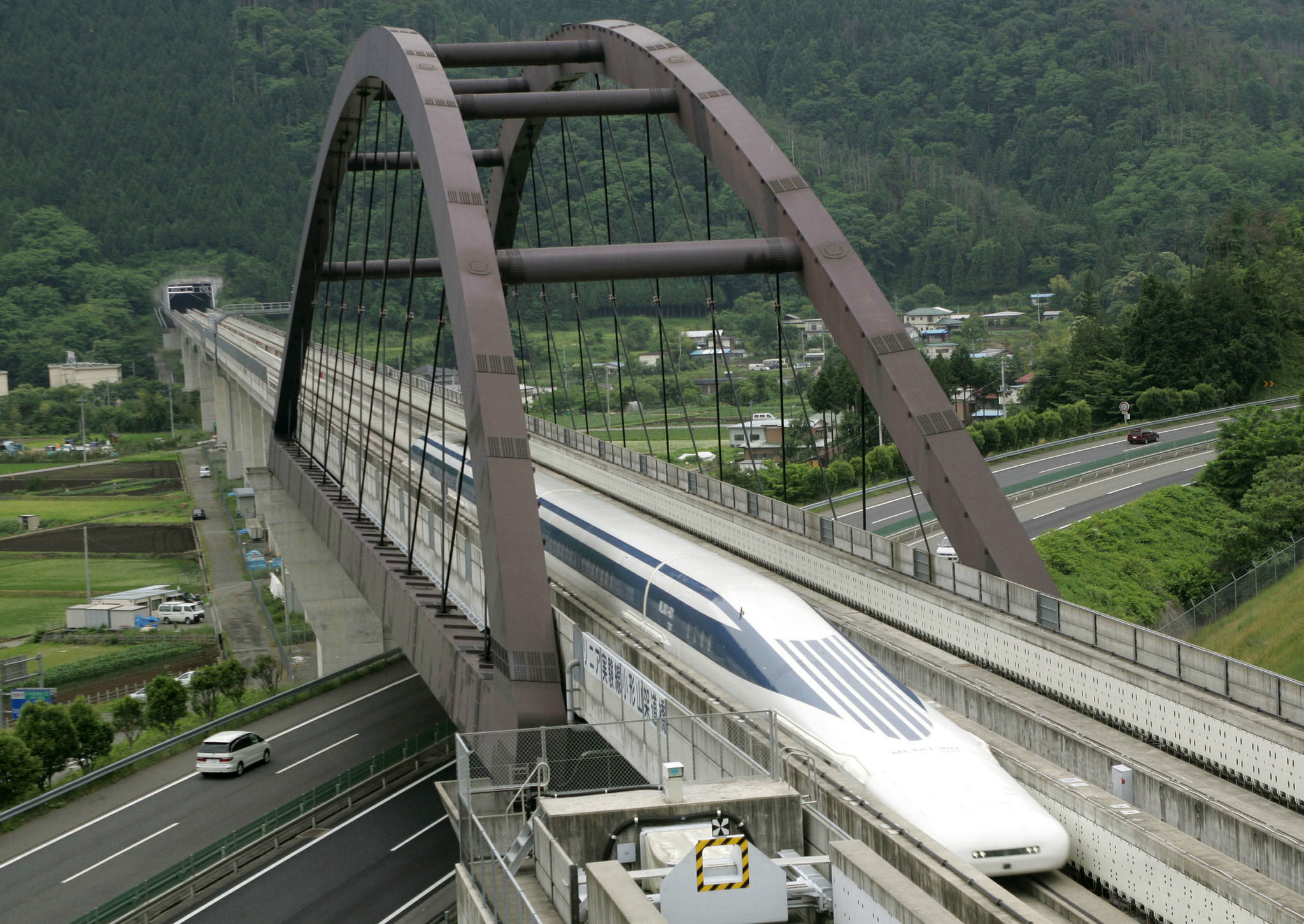Central Japan Railway Co.'s Maglev train, which is levitated and propelled forward by magnetic force, speeds at an 18.4 kilometre test track in Tsuru, west of Tokyo June 10, 2004.