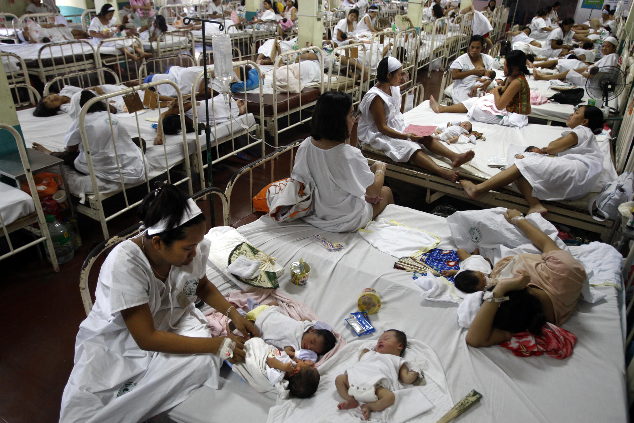 Women share beds after giving birth at Dr. Jose Fabella Memorial Hospital in Manila. The Philippine capital is one of the most densely populated places on Earth. A ban on contraception at public clinics there has put birth control out of the reach of most of the city's poor. (Rick Loomis / Los Angeles Times)