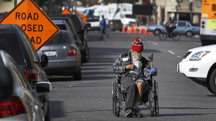 A man who said he was a Navy veteran pushes his wheelchair backward on skid row.  (Brian van der Brug / Los Angeles Times)