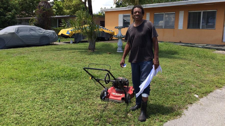 A bandaged Roger Butler stands in the Oakland Park yard where he said two dogs bit him Wednesday.
