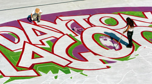 <p>Two artists paint the new logo for Daytona Lagoon on the base of the wave pool in 2004 when the park reopened after the previous version of the park, Adventure Landing, had closed.</p>