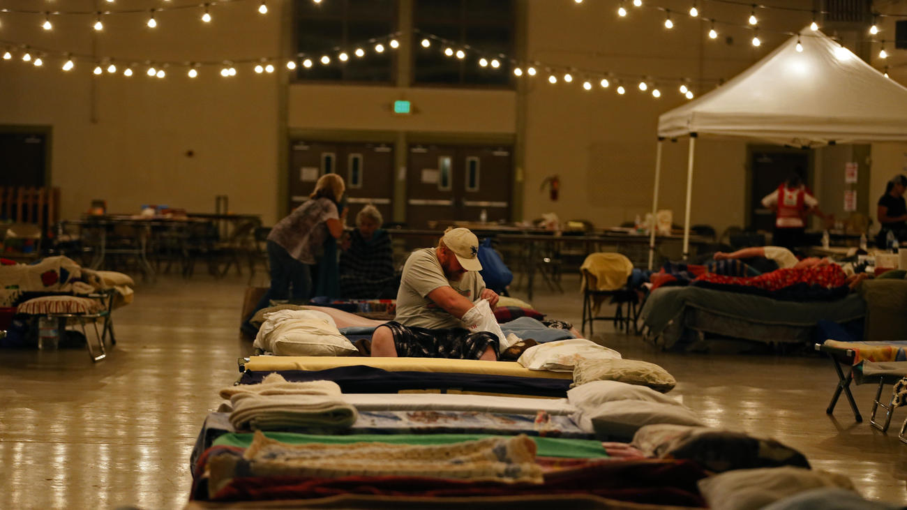 Dave Burns digs into a Red Cross toiletries bag before bedding down on a cot at the Napa County Fairgrounds evacuation center in Calistoga.  (Don Bartletti / Los Angeles Times)