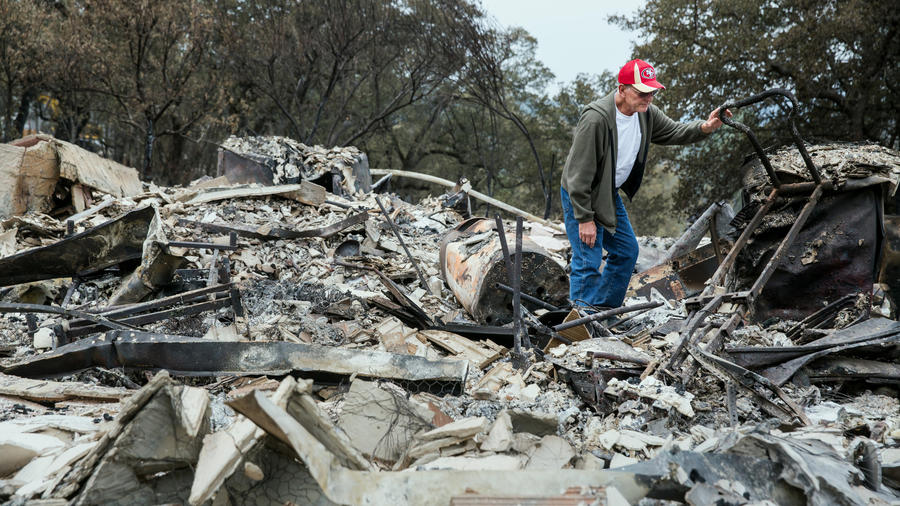 Jay Albertson searches through the rubble of his home of 30 years after it was burned by the Valley fire in Hidden Valley Lake, Calif.