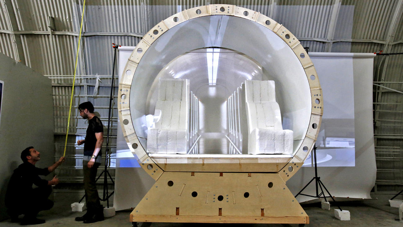 JJ Sansaone, left, and Andrew La Mendola take measurements for a backdrop of a Hyperloop capsule model.