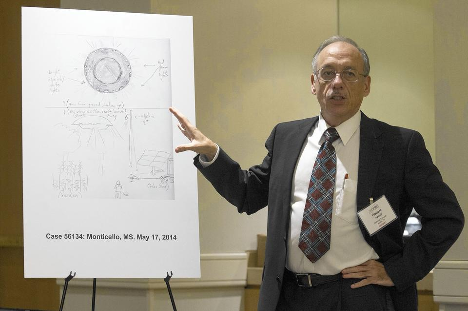 Robert Powell, the Mutual UFO Network's director of research, discusses a witness's illustration of a UFO sighting made on May 8, 2014, in Monticello, Miss., during a press conference at Hotel Irvine on Friday.