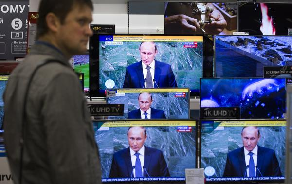 A man looks at television screens in a Moscow shop as Russian President Vladimir Putin addresses the United Nations on Sept. 28, 2015. (Pavel Golovkin / Associated Press)