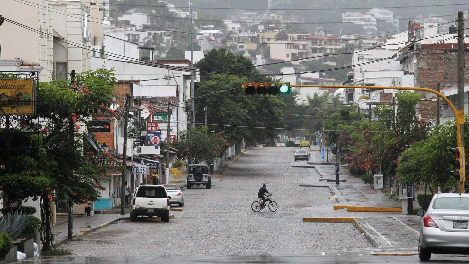 A cyclist rode along an empty street ahead of landfall in Puerto Vallarta. (AP)