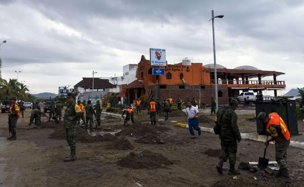 Soldiers and rescue workers begin to clean up a street in Manzanillo the morning after Hurricane Patricia made landfall. The storm brought far less damage than was initially feared. (Getty Images)
