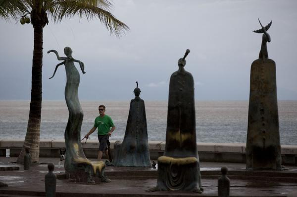 A man walks his dog in Puerto Vallarta, after Patricia mostly missed the Mexican tourist town. (Associated Press)