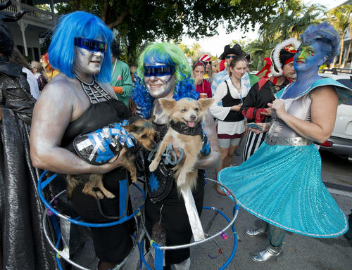 """In this Friday, Oct. 30, 2015, photo provided by the Florida Keys News Bureau, people and their dogs dresses as space creatures proceed down Fleming Street in Key West, Fla., during the Fantasy Fest Masquerade March. Thousands participated in the event that was one of the highlights of the subtropical island's annual Fantasy Fest costuming and masking festival that is to conclude Sunday, Nov. 1. This year's festival theme is """"All Hallows Intergalactic Freak Show."""" (Andy Newman/Florida Keys News Bureau via AP) ORG XMIT: FLAN110"""