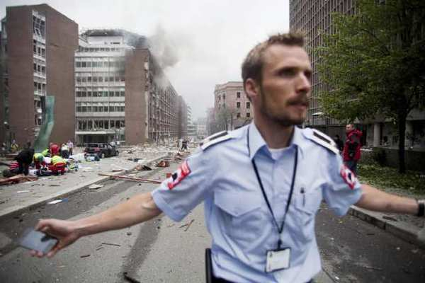 An official attempts to clear away spectators from buildings in the centre of Oslo following an explosion in July 2011. (Fartein Rudjord / Associated Press)